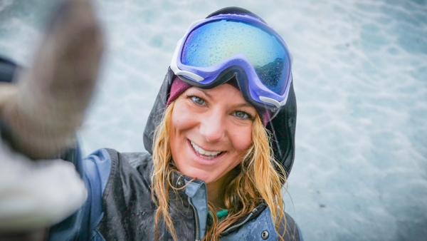 Snowboarder and blogger Alexa Hohenberg smiles for the camera by a wall of glacier ice