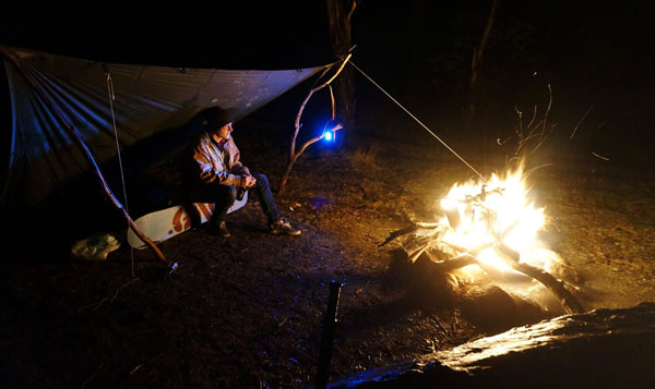 Simple living in Australia. Camping under a lean to by a bonfire.