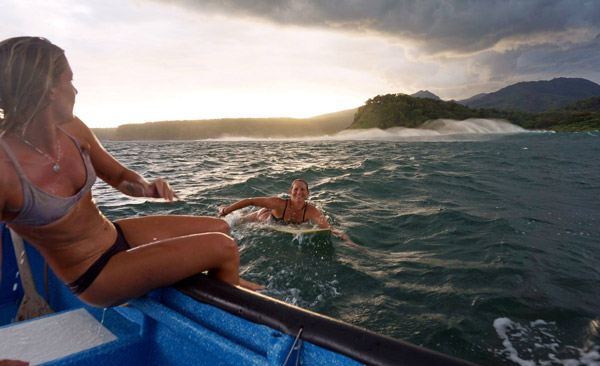 A happy surfer girl paddling back to the boat as a storm develops on the horizon