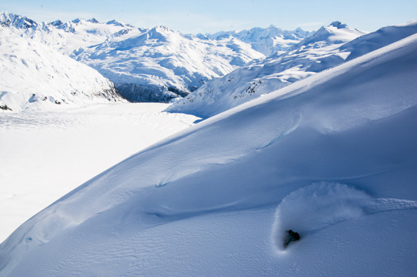 Snowboarder Alexa Hohenberg does a big powder turn in Alaska when heli skiing with Points North Heli Adventures
