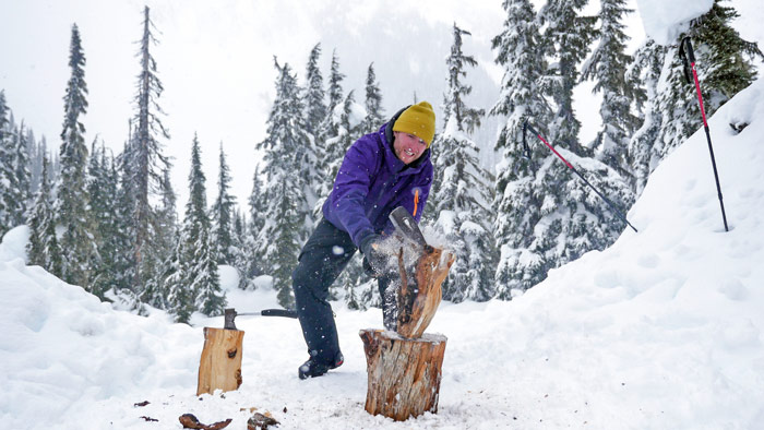 Chopping wood in the snow for the log cabin