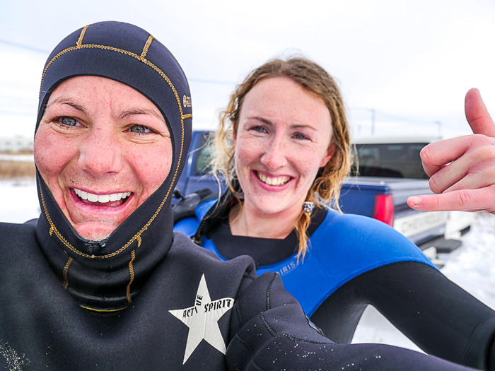 Surfer girls surfing in sub-zero water in The Sea of Japan