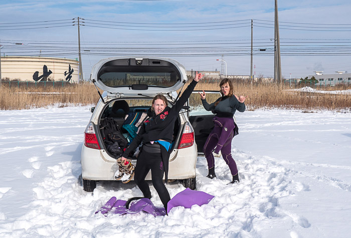 Surer girls changing on the beach in the snow