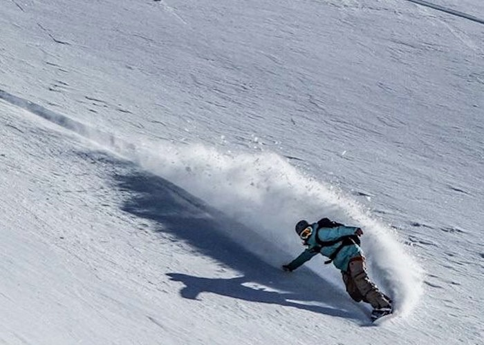 A snowboarder carves the mountin