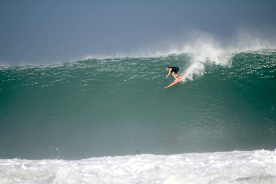 Woman surfing big wave