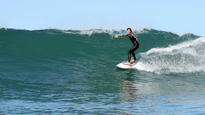Girl surfing a wave in wetsuit