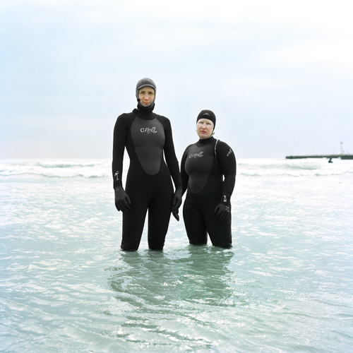 Two women surfers in cold water