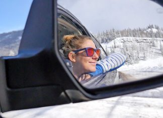 Girl looking out the window on a road trip through Colorado