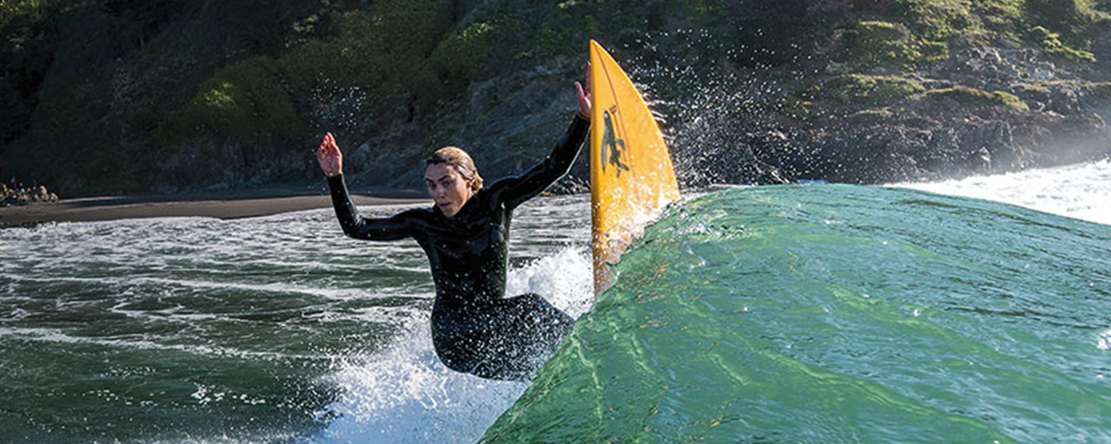 Winter surfing in a wetsuit - girl surfer