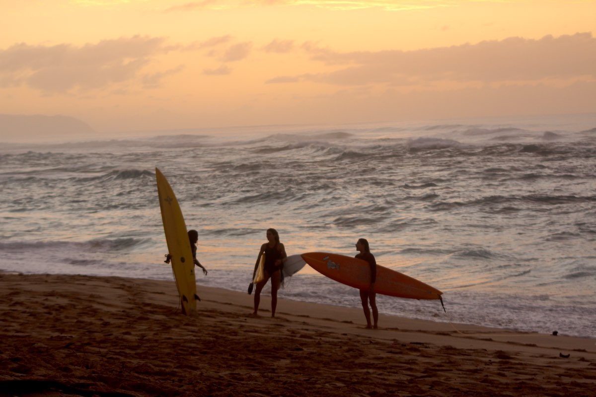 women on beach with surfboards at sunset
