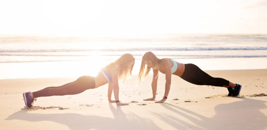two girls doing plank on the beach