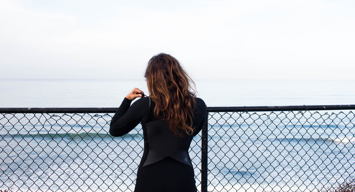 Girl putting on wetsuit